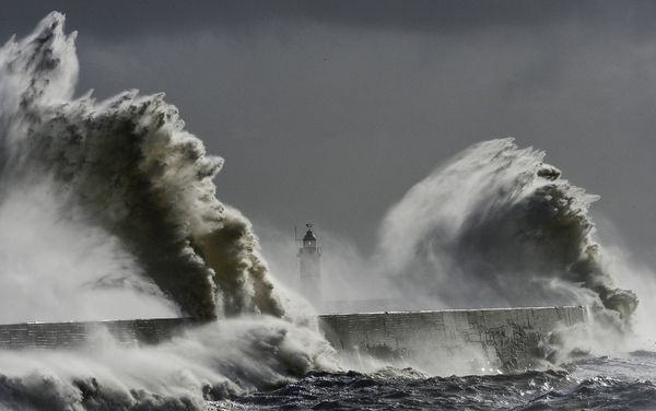 Waves hit a lighthouse in Newhaven, England, on February 15, amid record levels of flooding. More intense storms are an example of extreme weather brought on by climate change, experts say