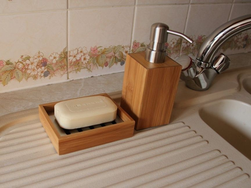 Bamboo lotion dispenser and soap dish in a kitchen